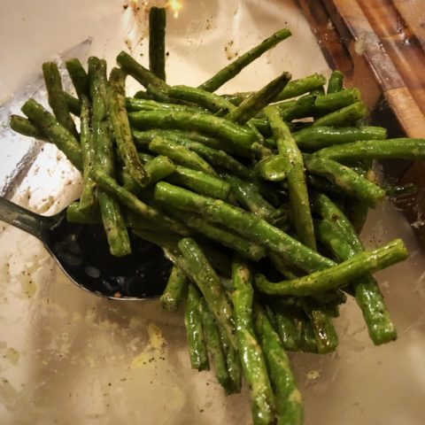 green beans in a clear bowl with spoon