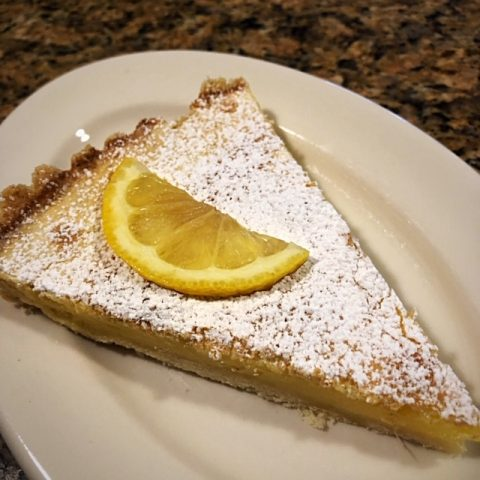 white plate with a piece of lemon tart and lemon wedge