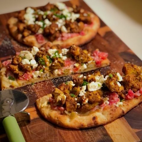 pizza on cutting board with cutter