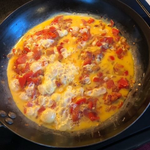 pan with eggs and tomatoes cooking