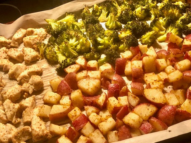 chicken, red potatoes and broccoli on a baking sheet
