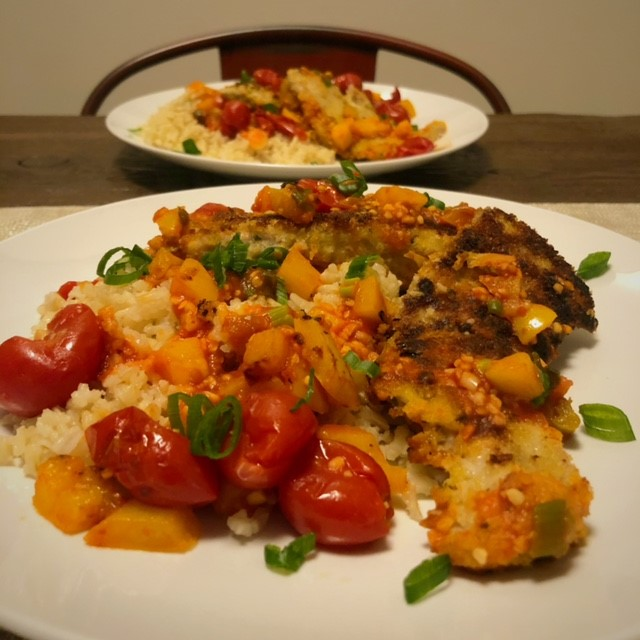 white plate with pork and tomatoes