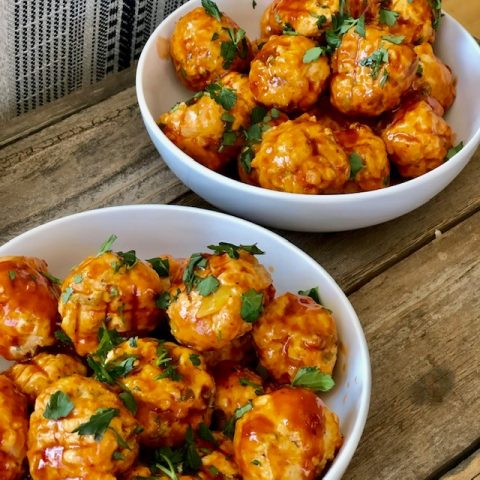 two bowls of buffalo chicken meatballs on a table