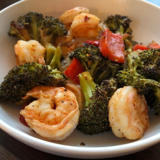 roasted shrimp, broccoli, red peppers and onions in a white bowl