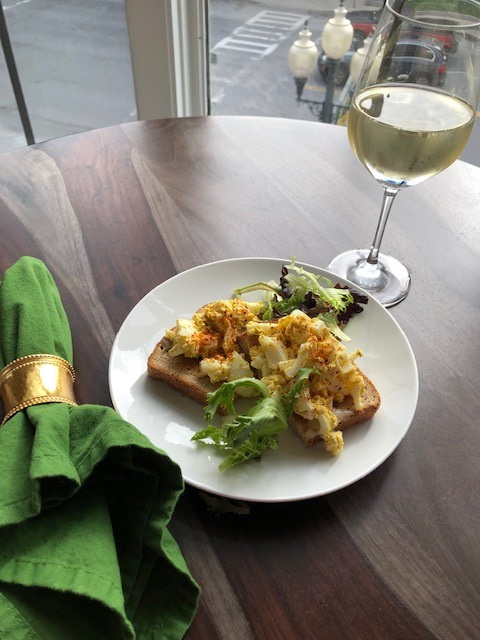 egg salad on a white plate with a green napkin and glass of white wine on a table
