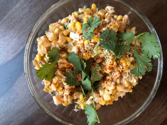 corn salad in a glass bowl on a wooden table