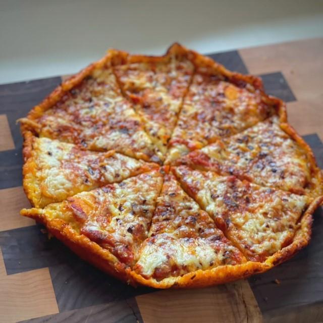 deep dish sliced pizza on cutting board