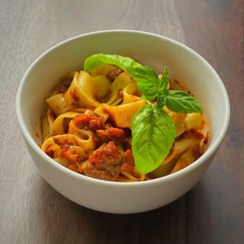 white bowl of mushroom bolognese over pasta with basil leaves