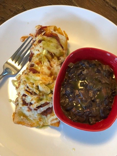 enchilada with black beans in a red bowl on a white plate