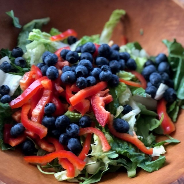 mixed salad, blueberries, red peppers in a brown bowl