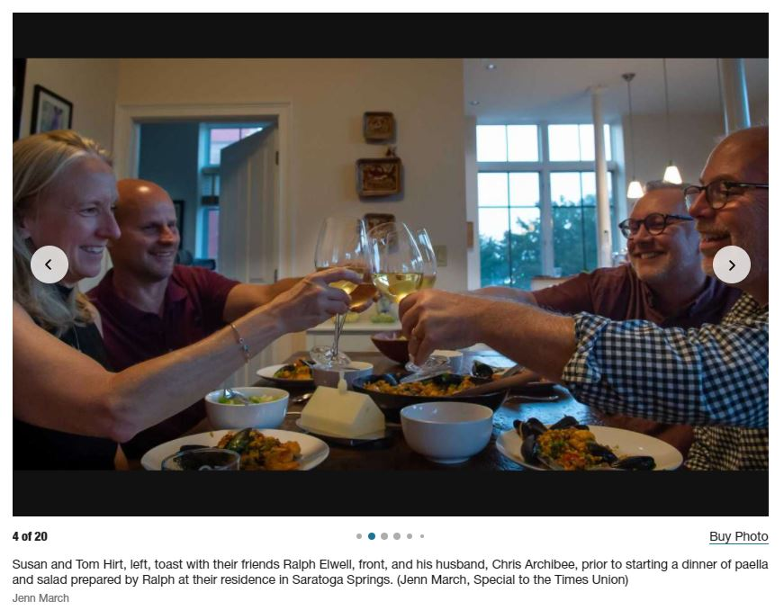 four people toasting white wine over the dinner table