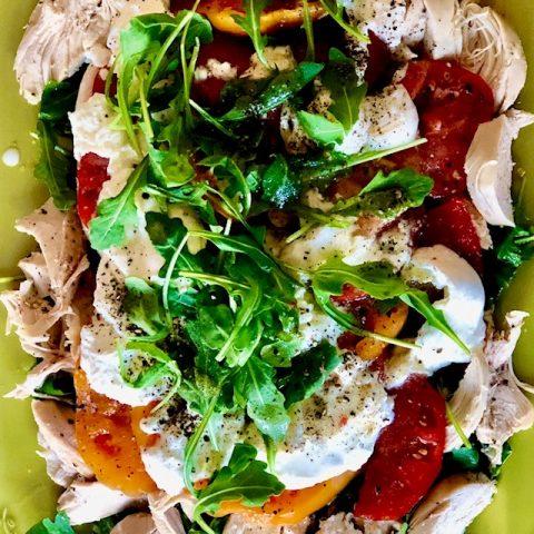 heirloom tomato, burrata and arugula on a green plate